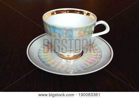 A white iridescent tea cup and saucer