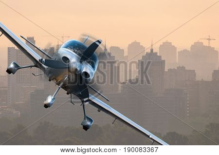 Aircraft traveling over city buildings and high-rise skyscrapers. Concept of privat airline travel business and civil aircrafts.