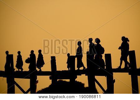 Silhouette of people walking on U Bein bridge in Amarapura, Myanmar.