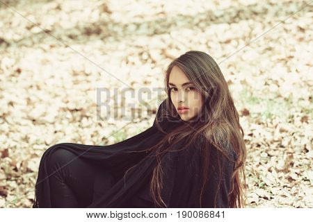 Girl With Long, Brunette Hair Sitting On Ground