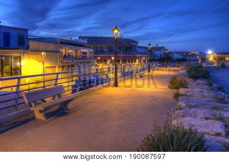 Promenade near mediterranean sea by night, Saintes-Maries-de-la-mer, Camargue, France, HDR