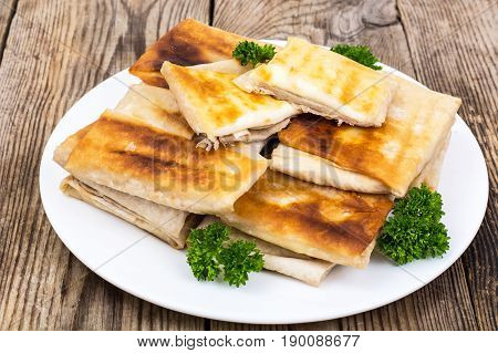White plate  with envelopes of thin Armenian bread lavash fried with crispy crust. Filling of cheese and greens for hot breakfast. Studio Photo