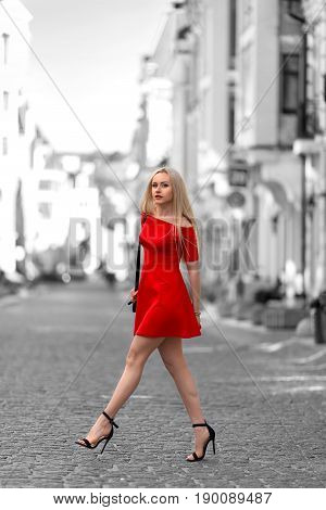 Beautiful blonde woman in the red dress and high heels walking outdoor. Partly desaturated picture.