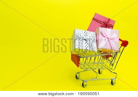 Mini Colorful Gifts Box In Mini Supermarket Shopping Cart On Yellow Background, Holiday Sale Concept