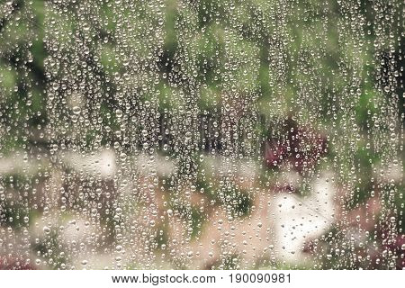 raindrops on home window glass with green forest background