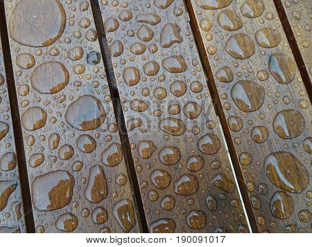 Large and small raindrops on wooden table top