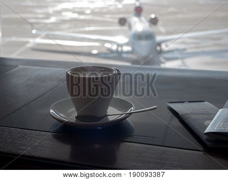 Cup of coffee in airport's business lounge with aircraft.