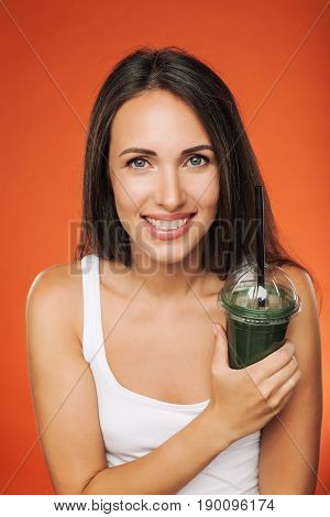 Young attractive brunette woman holding takeaway cup of smoothie. Happy girl posing on red background. Healthy eating concept.