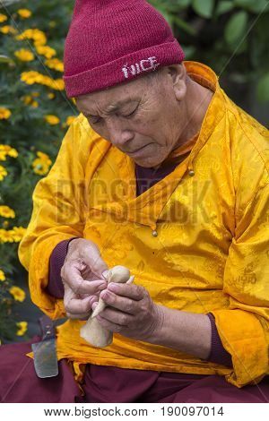 HIMALAYAS ANNAPURNA REGION NEPAL - OCTOBER 13 2016 : Tibetan monk sculpted figure of the deity of barley flour tsampa for Buddhist religious ceremony in Nepal. Close up