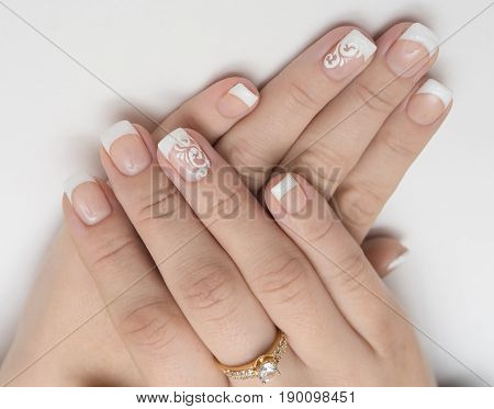 Two hands of woman with manicured and painted fingernails for spa treatment concept