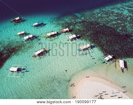 Aerial top view of tropical island beach with boats and people. Palawan