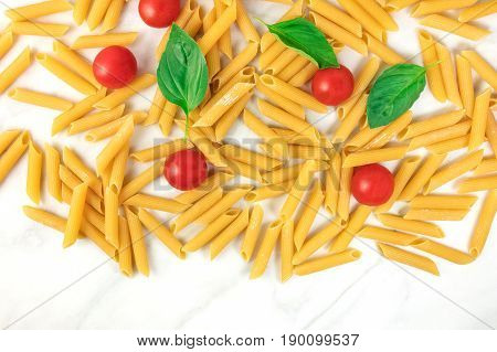 Penne rigate, shot from above on a white marble table with a place for text. An overhead photo of a texture of pasta, basil leaves, and cherry tomatoes
