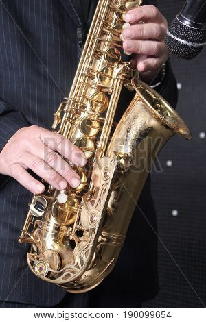 A golden and beautiful saxophone in the hands of a musician