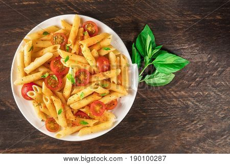 An overhead photo of a plate of pasta with tomato sauce. Penne rigate with cherry tomatoes and fresh basil leaves, on a dark rustic texture with a place for text