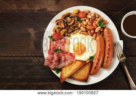 An overhead photo of a plate of English breakfast on a dark rustic texture, with a sunny side up egg, sausages, bacon, toasts, grilled mushrooms and tomatoes, a cup of black coffee, and copy space