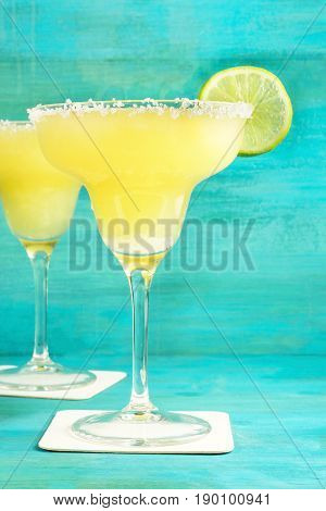 Lemon Margarita cocktails with wedges of lime on a blue background with copy space