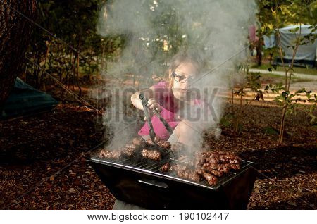 Little caucasian girl (elementary age) cooking the ćevapi (a grilled dish of minced meat a type of skinless sausage) on barbecue grill outdoor. Summer camping active recreation and touristic concept.