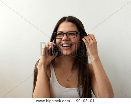 Girl in glasses is talking happily on the phone. Laugh. White background
