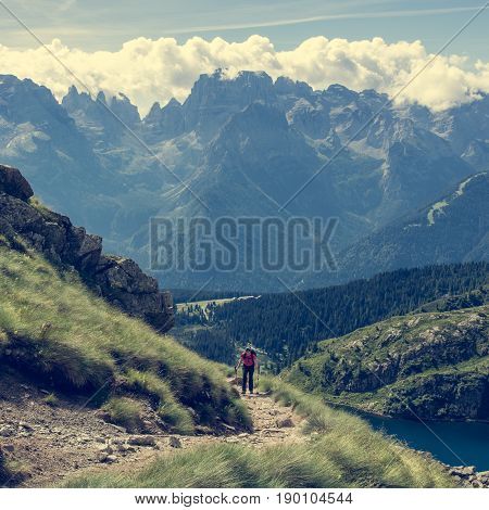 Trekker walking a picturesque mountain trail. Brenta group in Italy.