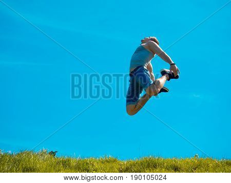 Jumping up guy. Background blue sky. Below the green grass.