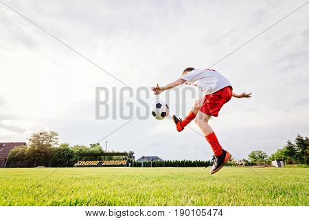 8 Years Old Boy Child Kicking Ball On Playing Field.