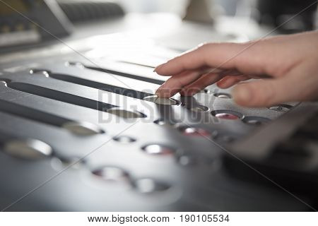 Female radio host using adusting volume at music mixer in radio studio