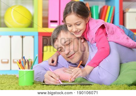 Father and daughter lying on floor and drawing pictures