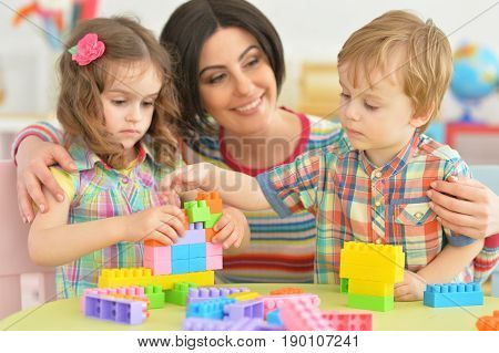 Mother playing with her little children in room