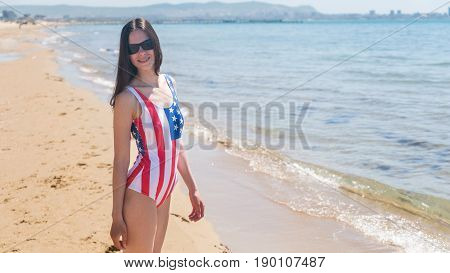 A slender young woman in a US flag walks along the coast.