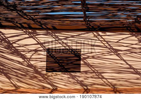 Roof terrace shaded from the sun by a steel lattice creating shadow pattern on a ocher wall