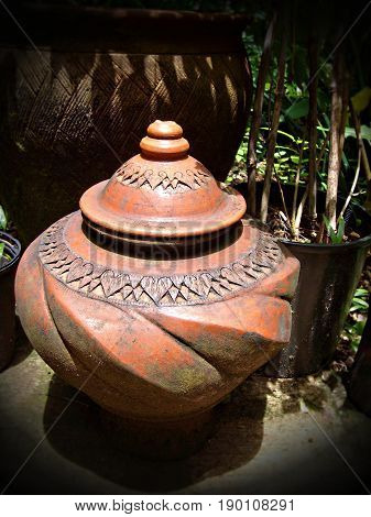 earthen jar in a garden A big earthen jar with decorative designs and cover placed in a garden