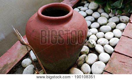 one earthen jar with white stones in a garden one big red earthen jar on the ground surrounded by smooth white stones