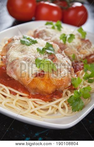 Parmesan chicken with melted cheese an tomato sauce served over spaghetti pasta