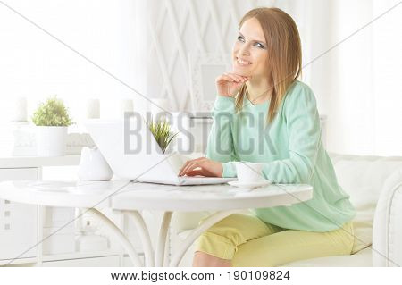 Beautiful young woman sitting at table and using laptop