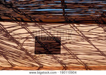 Roof terrace shaded by a steel lattice creating shadow pattern on a ocher wall