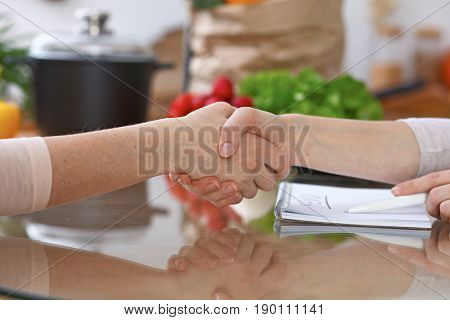 Handshake in the kitchen, closeup. Two women agreed about menu. Cooking and friendship concept