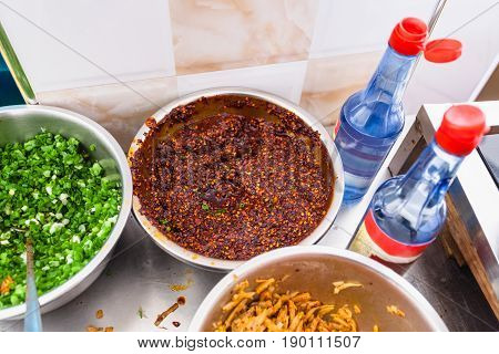 Above View Of Bowls With Spicy Toppings On Kitchen