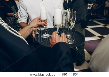 People Toasting With Champagne Glasses At Wedding Reception, Waiter Serving On Tray Champagne Drinks