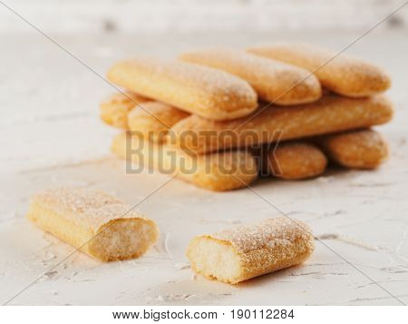 Close up view of ladyfinger biscuit cookie on white concrete background. Italian cookie savoiardi.
