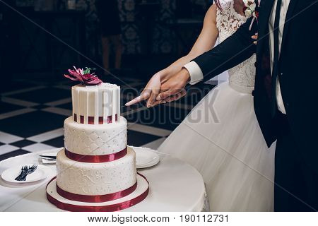 Bride And Groom Cutting Wedding Cake. Wedding Couple Tasting Big Delicious Cake With Pearl And Red F
