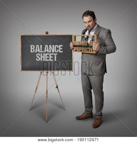 Balance sheet text on blackboard with businessman and abacus