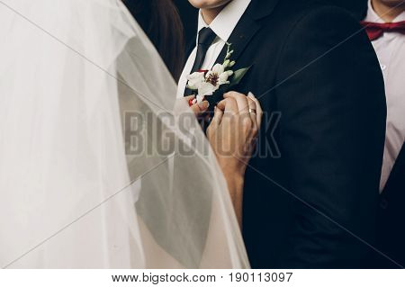 Bride Putting On Groom Boutonniere Of Red White Flowers Close Up On Jacket