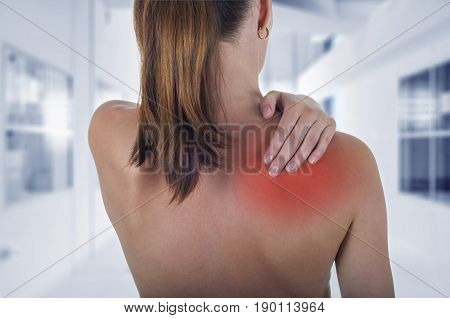 Woman with shoulder pain back hospital background