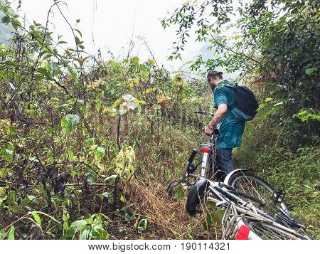 travel to China - bicyclist on overgrown of karst mountain in Yangshuo County in spring season