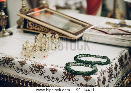 Golden Crowns And Green Wreaths On Altar In Church During Wedding Ceremony