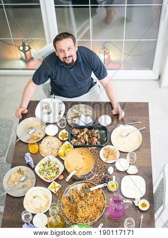 Man sitting on the table with food leftovers after Ramadan Iftar