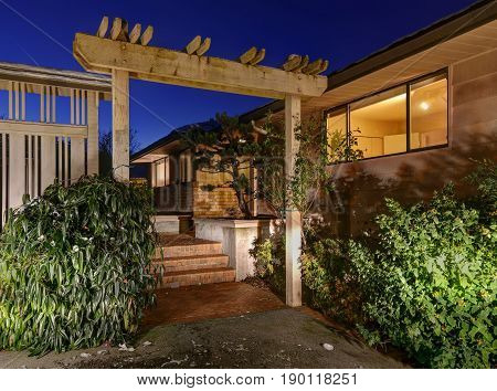 Sunset View Of Two Story Home With Decorative Pergola