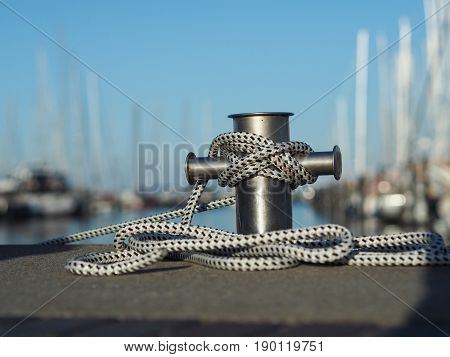 Stainless steel bollard with rope in a luxury marina soft bokeh with luxury boats and yachts