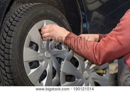 Mechanic removes trim cap at car tires before a tire change
