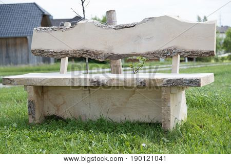 Massive garden bench made of solid wood invites to a break
